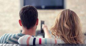coppia sul divano guarda la tv